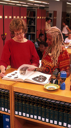 The African Art librarian reviews illustrations with a reader at the National Museum of African Art Library